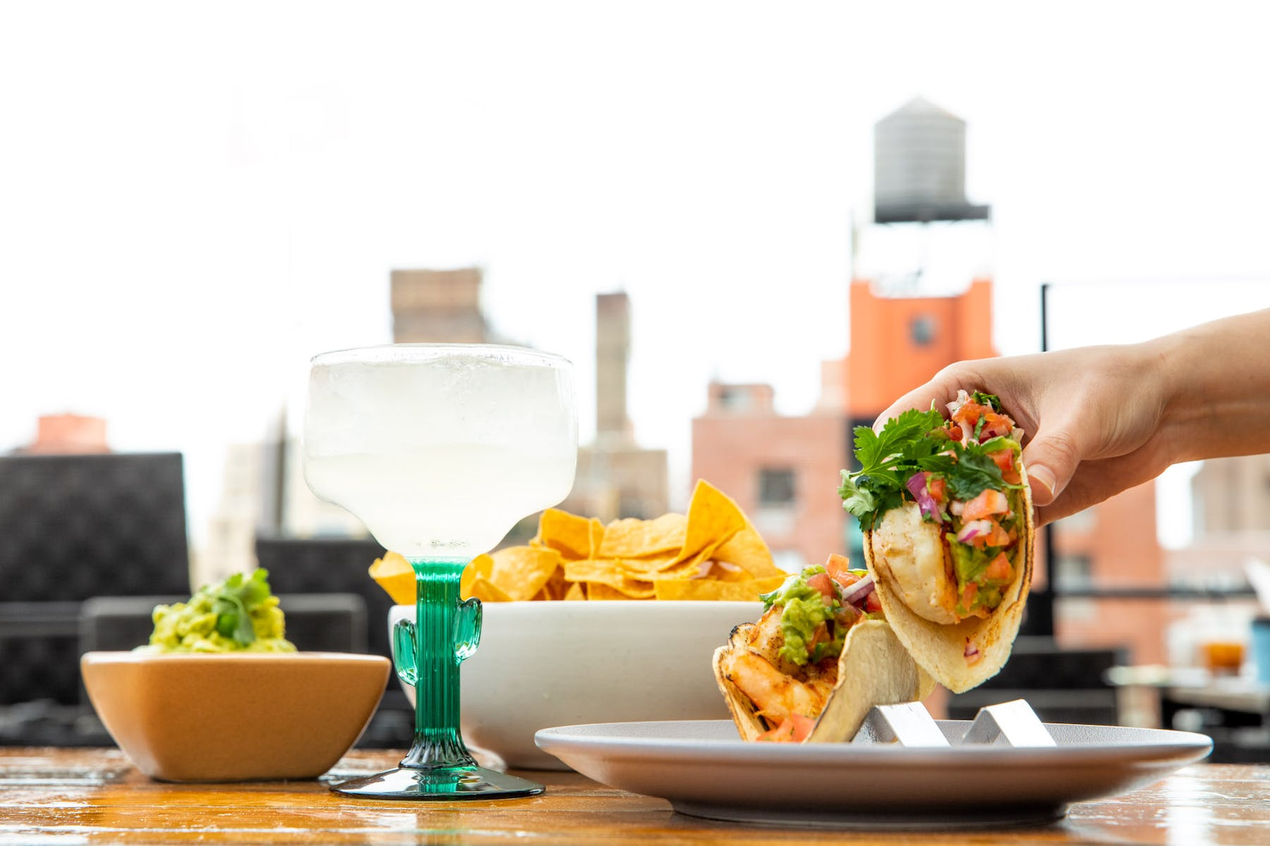 A hand holding a taco with a bowl of chips and guac on the side, and a cocktail