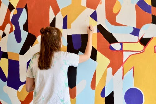 a lady painting a wall