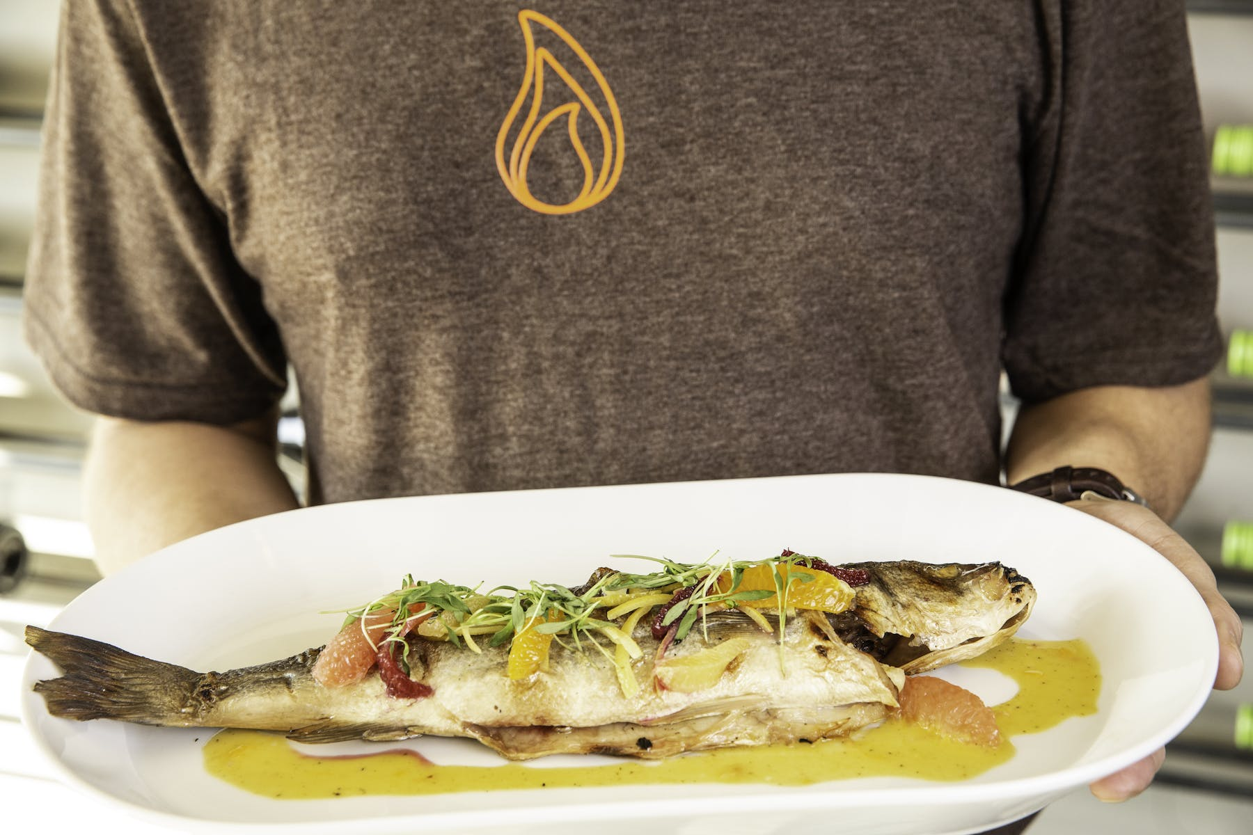 a man holding  a whole fish on white plate with oil drizzled over