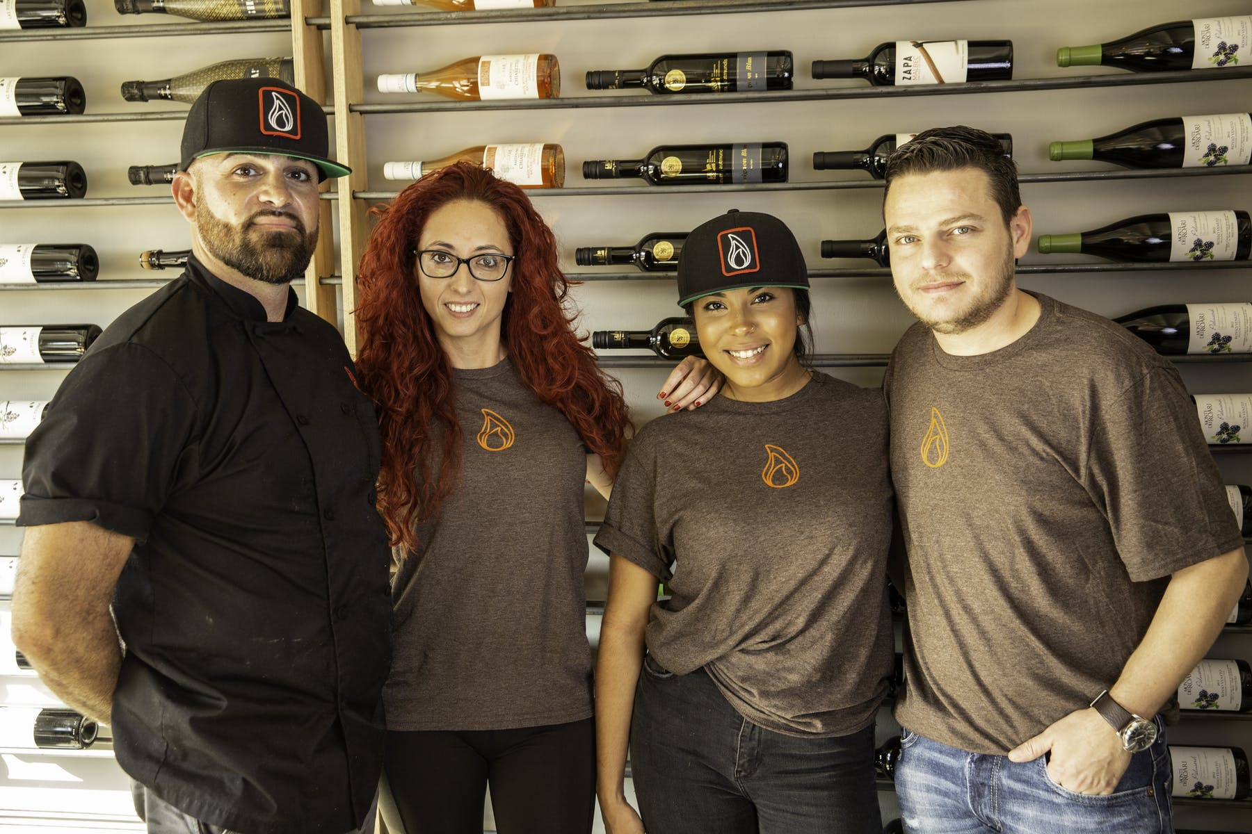 4 employees in logo shirts standing next to each other in front of a wall with wine bottles