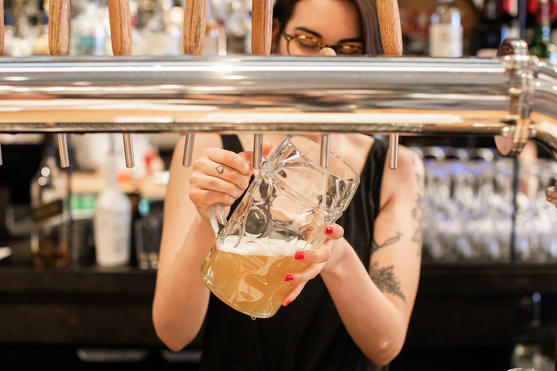 a woman pouring beer into a glass