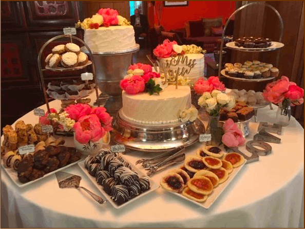 table full of cakes, cookies, and cupcakes