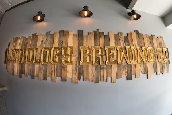 wooden slated sign on grey wall under light sconces