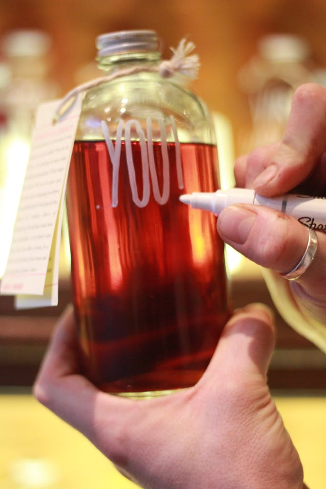 "closeup of glass bottle filled with red cocktail with someone writing ""you!"" in white marker"