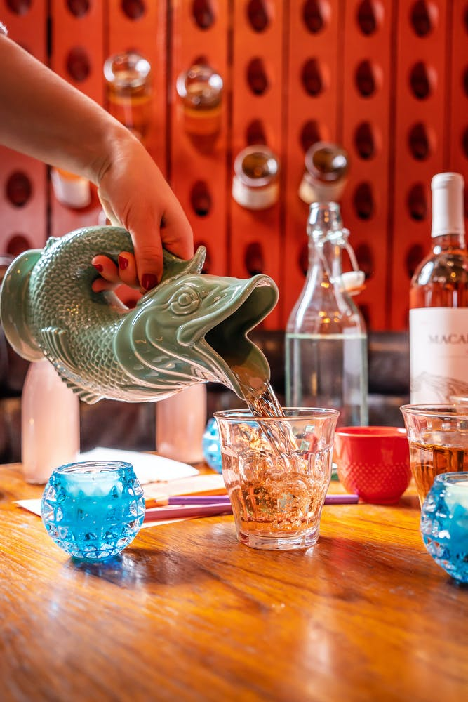 rose wine being poured from a teal fish pitcher into a glass