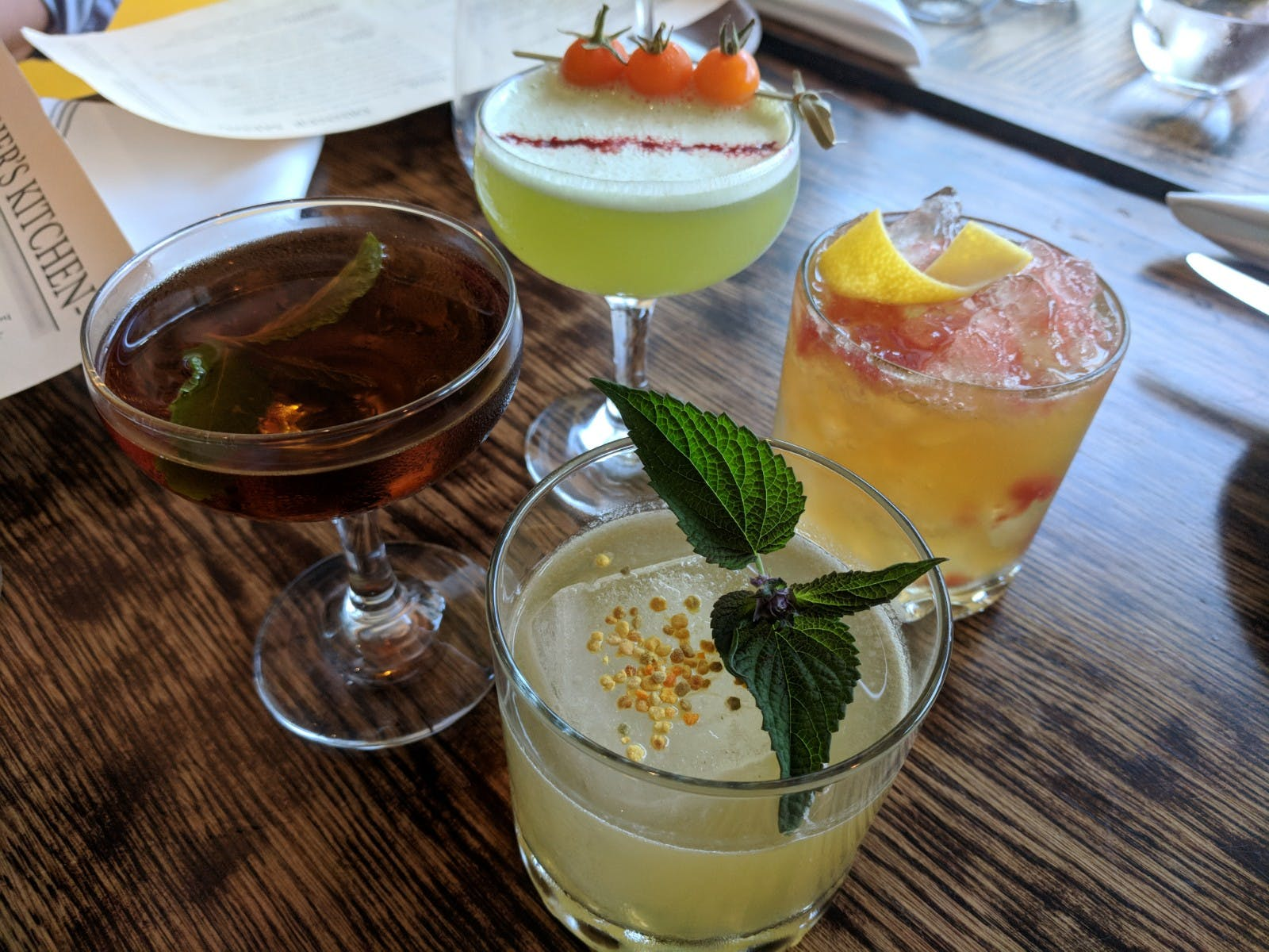 4 different cocktails with fruits and leaves