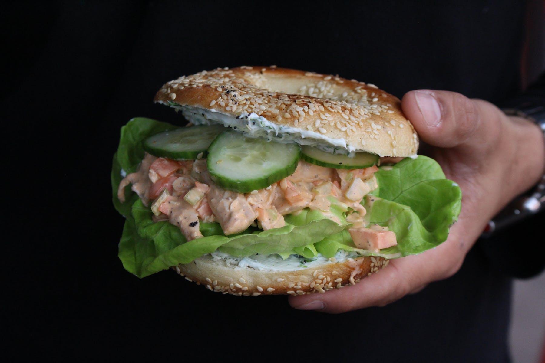 a hand holding a sandwich