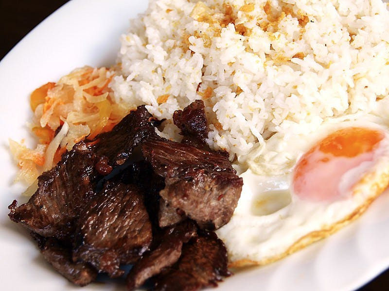 Filipino dish with beef slices, fried garlic rice, and fried egg