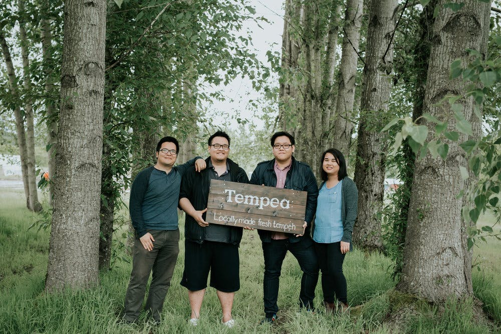 4 people holding a wooden sign that says tempon