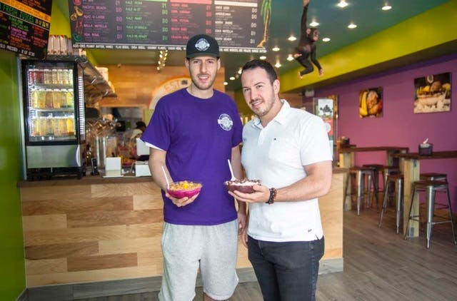 Two man holding Acai Bowls