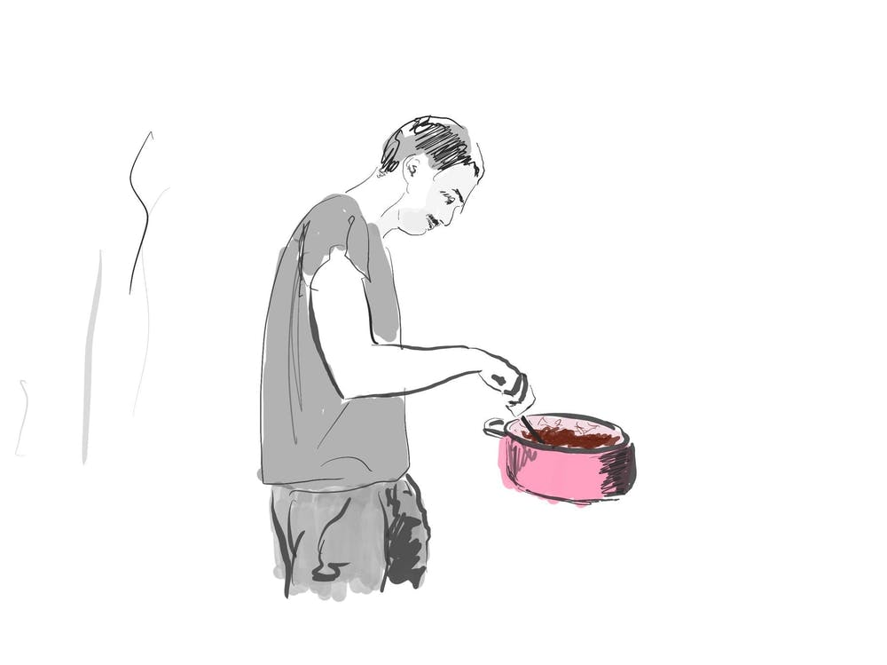 Man stirring pot of food