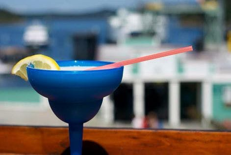 margarita served in a blue glass with a lime and a blue ocean can be seen in the background