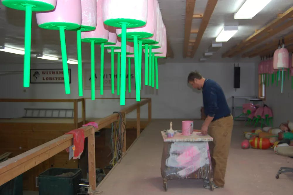 Josh Miller, president of the Tenants Harbor Fisherman's Co-op repaints his buoys to prep for the coming season.