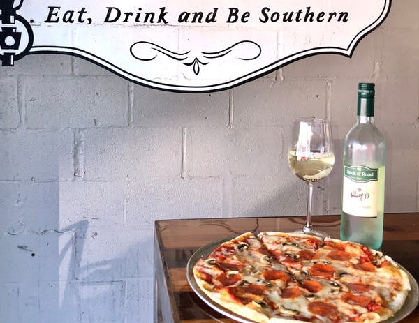 Pizza and bottle of wine with a glass on the side