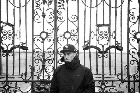Black and white picture of young man standing in front of a gate