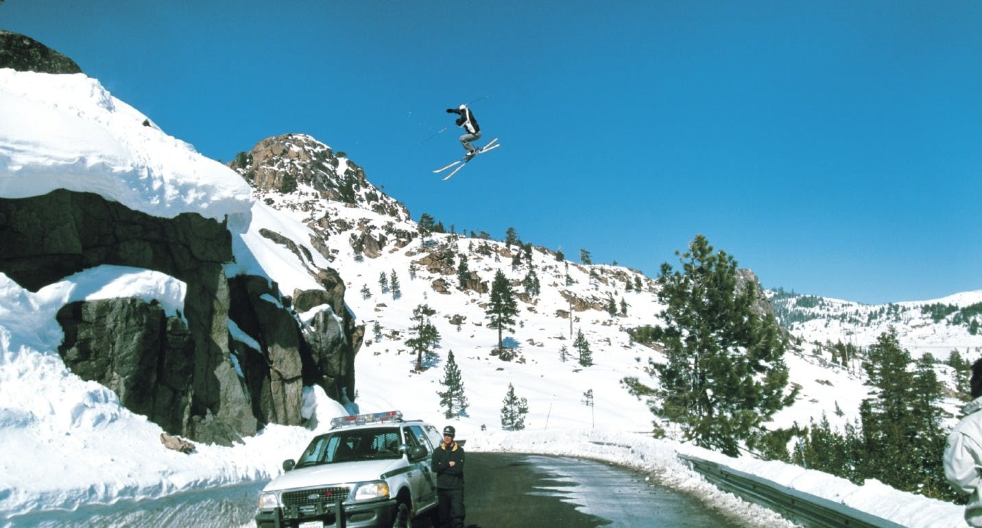 image of a skier jumping over the mountain road