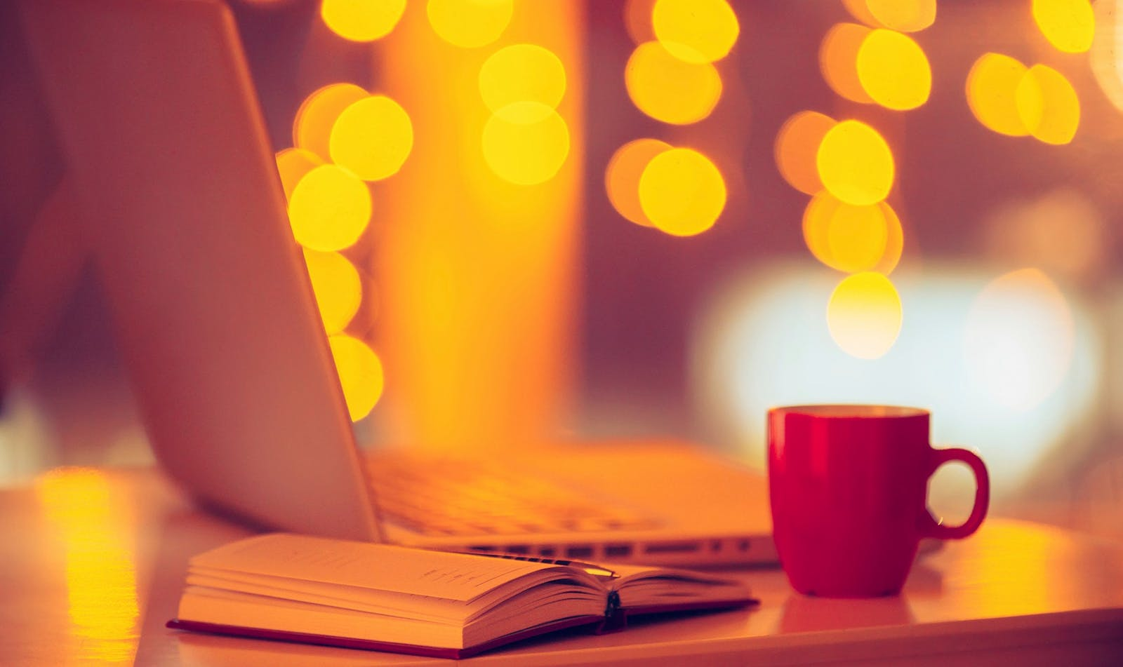 Laptop & cup with twinkle lights in background